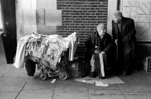 Elderly homeless couple with goods loaded on pram - Embankment Tube Station, London
